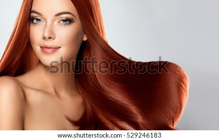 Beautiful model girl with shiny red  straight long  hair . Care and hair products .