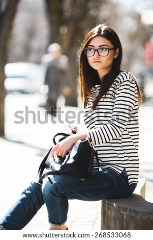 Beautiful model in a striped sweater and is talking on the phone. - stock photo