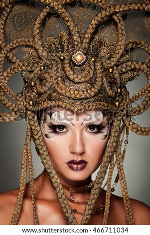 Beautiful model in fashionable makeup and original handmade crown.