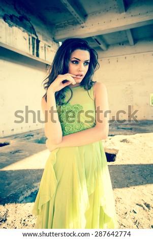 beautiful model in green dress posing in grunge location  - stock photo
