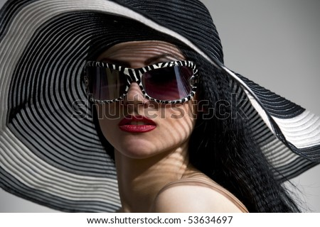 Beautiful model in striped hat and top with glasses on the gray  background - stock photo