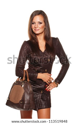 Beautiful model in stylish coat with bag on the isolated background