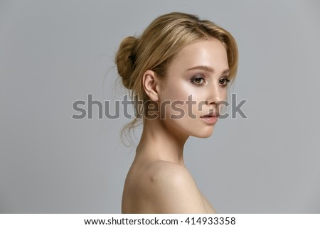 beautiful model lady with natural make-up and blonde hair studio fashion shot on gray background, perfect skin - stock photo