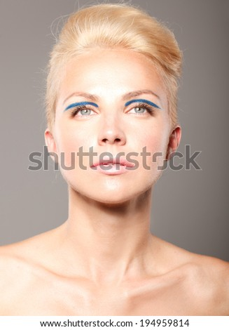 beautiful model lady with natural make-up and blonde hair studio fashion shot on grey background, perfect skin