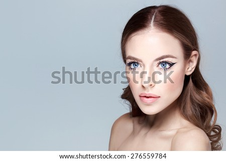 beautiful model lady with natural make-up and brunette hair studio fashion shot on grey background, perfect skin. Blue eyes - stock photo