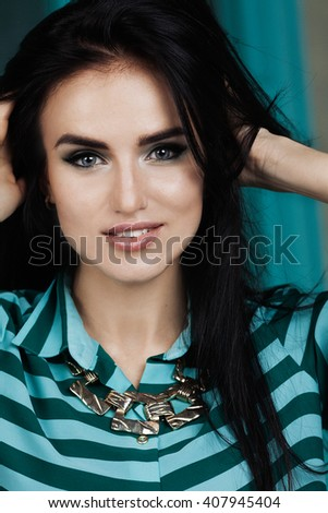 Beautiful model lady with professional makeup. Brunette hair and blue eyes. Studio shot. Perfect skin.