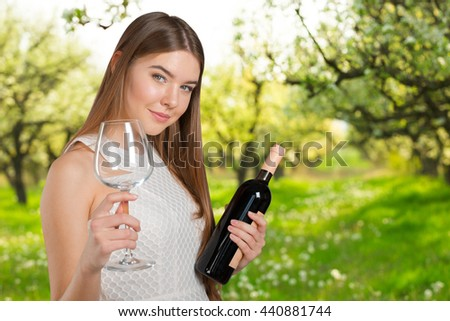 Beautiful model portrait isolated over studio background holding wine glass