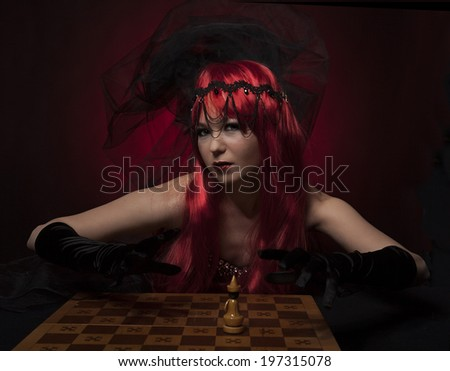 beautiful model posing as chess queen - fashion and beauty concept, Making a chess move - stock photo