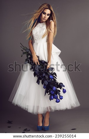 beautiful model posing in wedding dress with blue roses in her hands - stock photo