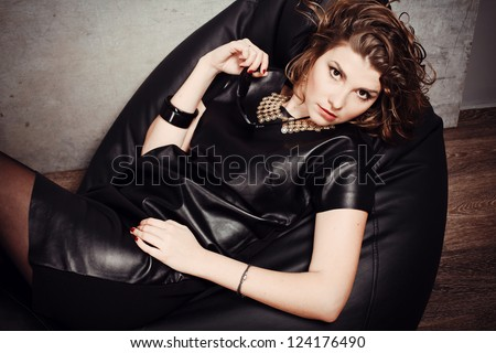 beautiful model posing lying in the studio in leather dress fashion - stock photo