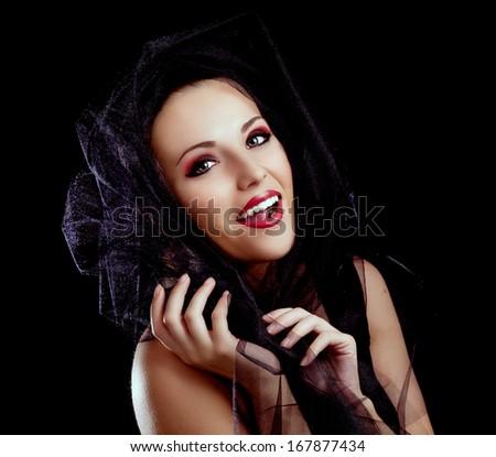beautiful model posing with black veil, against black studio background - stock photo