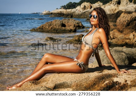 Beautiful model relaxing on a beach in Costa Brava, Spain. - stock photo