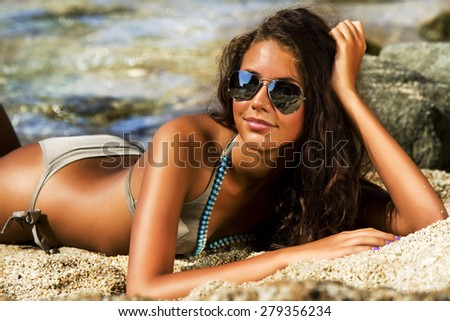 Beautiful model relaxing on a beach in Costa Brava, Spain. - stock photo