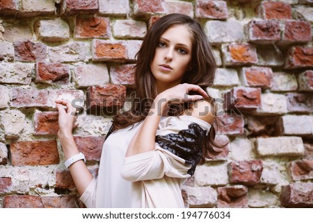 Beautiful model standing near old brick wall looking at camera - stock photo