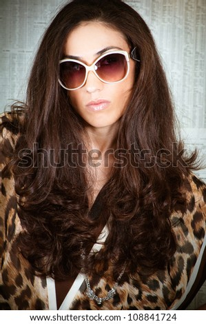 Beautiful model wearing eighties style fashion clothes on a newspaper background