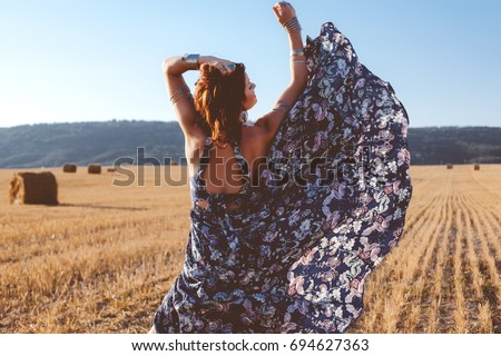 Beautiful model wearing summer cotton maxi dress and bracelets posing in autumn field with hay stack. Boho style clothing and jewelry.