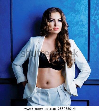 beautiful model with amazing long hair wearing a white suit and black bra - stock photo
