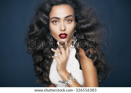 Beautiful model with elegant hairstyle and glamorous jewelry . Attractive woman with fashion wavy hairstyle and colourful makeup over blue background. Studio shot, Horizontal