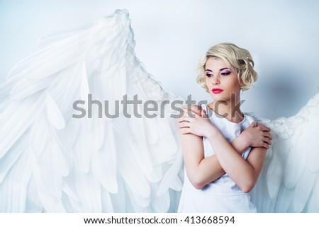 beautiful model with makeup and angel wings - stock photo