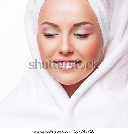 beautiful model with makeup wrapped into a bath towel, against white background - stock photo