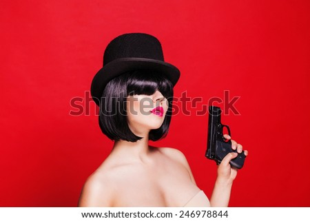 beautiful model with pistol in hat cylinder, on red background - stock photo