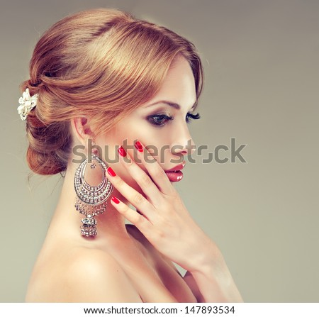 Beautiful model with red manicure and elegant hairstyle - stock photo