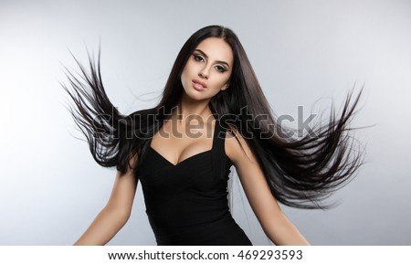 Beautiful model with smooth flying hair. fashion portrait of a brunette woman in a black dress