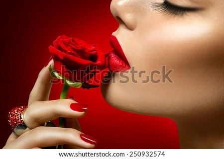 Beautiful Model woman kissing red rose flower. Red Lips, Nails and Rose. Beauty Girl. Makeup and Manicure. Sensual Mouth. Sexy Red Color Lips. St. Valentine's Day design. Part of Face - stock photo