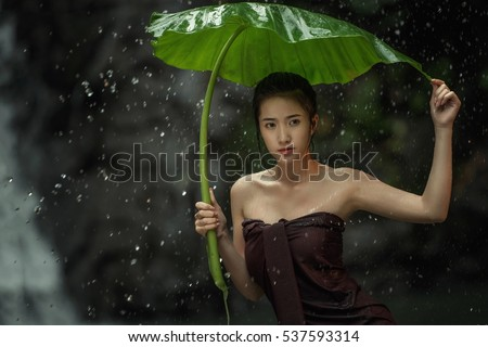 Beautiful Model Woman with splashes of water. Having shower under tropical Waterfall, Thailand