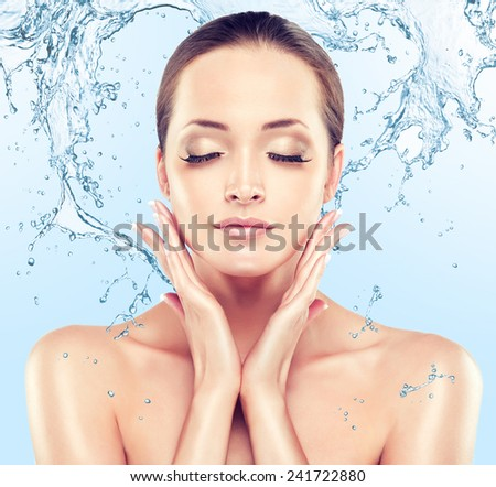 Beautiful model woman with splashes of water in her hands - stock photo