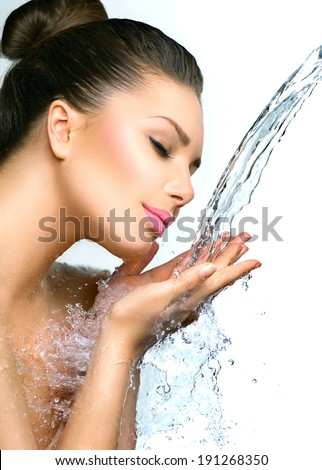 Beautiful Model Woman with splashes of water in her hands. Beautiful Smiling girl under splash of water with fresh skin over blue background. Skin care Cleansing and moisturizing concept. Beauty face  - stock photo