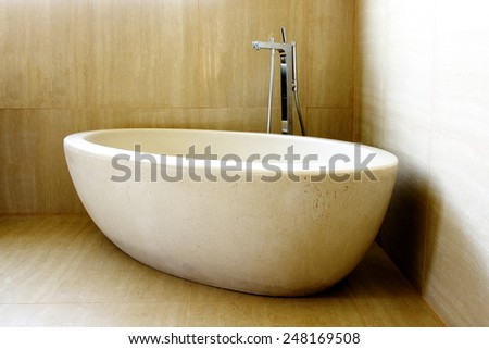 Beautiful Modern Bathtub and Tap in the Corner of Tiled Bathroom - stock photo