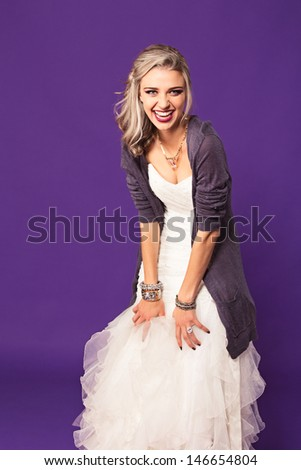 beautiful modern bride with blond long hairstyle wearing fashion accessories and ruffles silk ivory dress on purple studio background  - stock photo