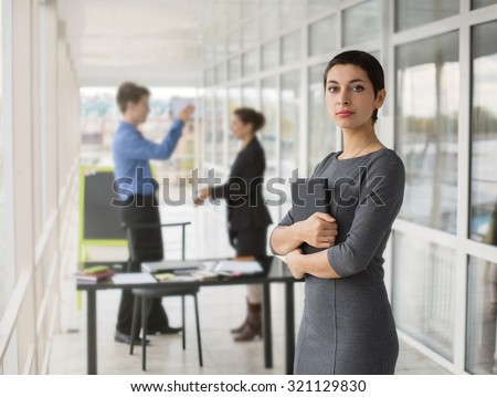 Beautiful Modern Businesswoman holding Tablet computer with colleague in Office on Background. Brainstorming, team working - stock photo
