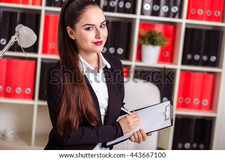 beautiful modern businesswoman in her office with a paper folder  - stock photo