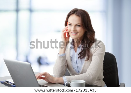 Beautiful modern businesswoman working on her laptop in office and having a phone conversation.