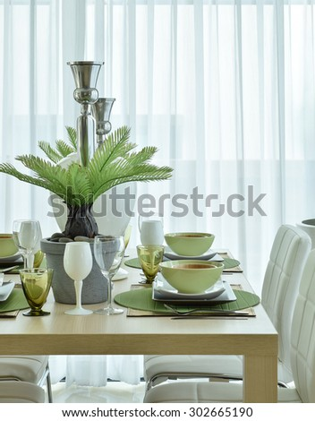 Beautiful modern ceramic tableware in green color scheme setting on dining table