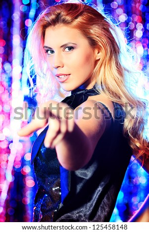 Beautiful modern girl dancing at the party. Disco lights.