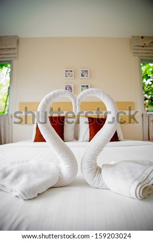 Beautiful modern home and hotel bedroom interior design with swans from the towel on the bed - stock photo