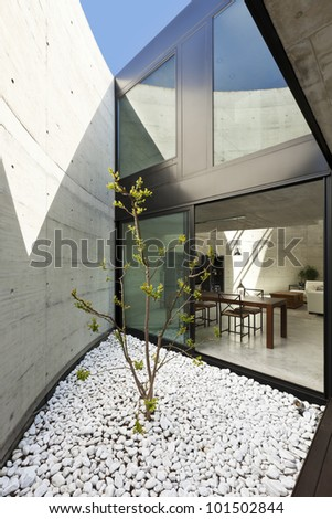 beautiful modern house in cement, dining room view from the veranda - stock photo