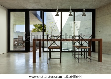 beautiful modern house in cement, interior, wooden dining table - stock photo