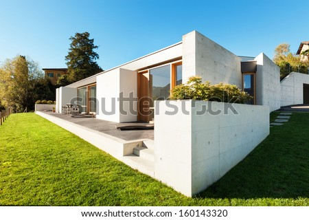 beautiful modern house in cement, view from the garden - stock photo