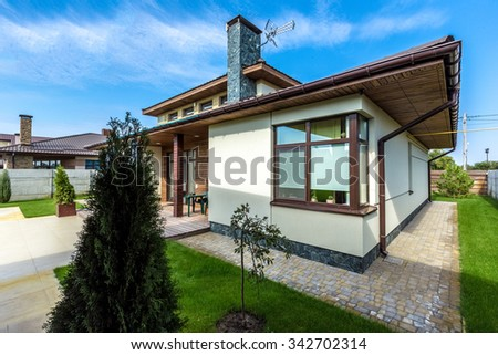 Beautiful modern house in cement, view from the garden. - stock photo