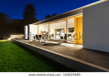 beautiful modern house in cement, view from the garden, night scene