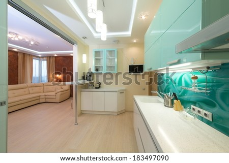 Beautiful modern kitchen overlooking the living room with sofa - stock photo