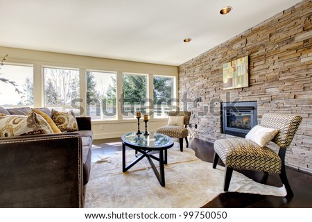 Beautiful modern large bright living room with dark floor and stone wall. - stock photo