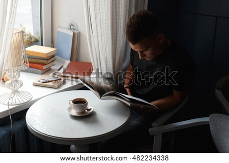 Beautiful modern man rest in a restaurant, reading a book and drinking coffee.