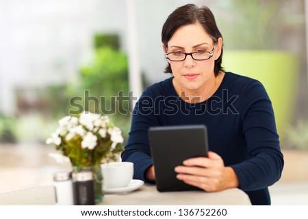 beautiful modern mature woman using tablet computer - stock photo