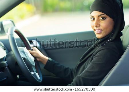 beautiful modern muslim woman in a car - stock photo
