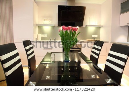 Beautiful modern nordic kitchen with modern lighting and fresh flowers - stock photo